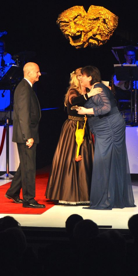 Brandi Baldwin, right, hugs Marieda Kilgore while Mark Wilson looks on. Wilson and Kilgore presented the award for Best Props at the 2012-2013 Montie Awards Ceremony where Baldwin earned her first and second awards.